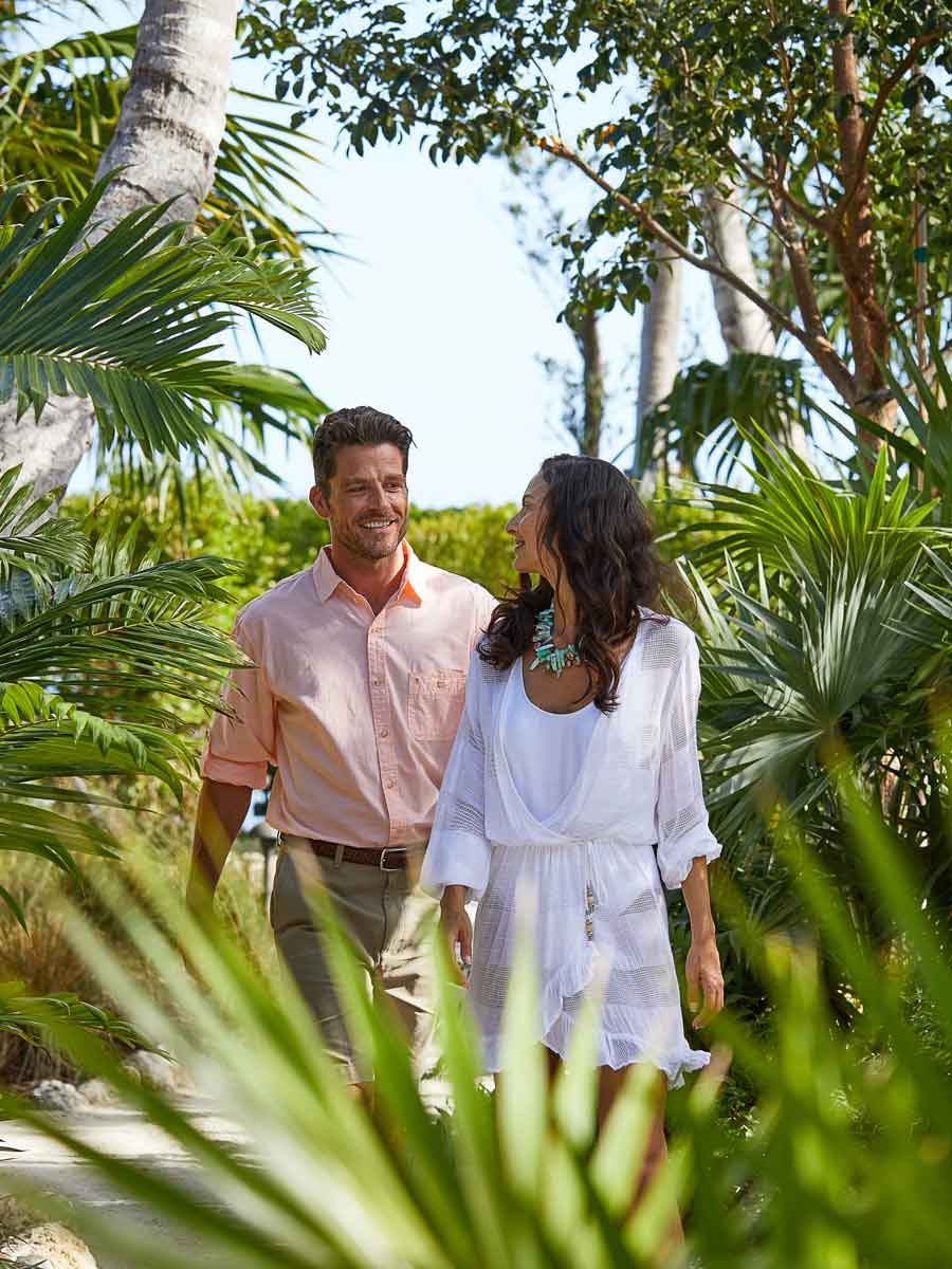 Couple walking in the greenery near the beach.